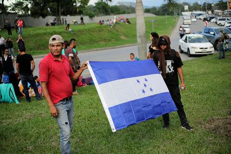 Hondurans hold a flag of Honduras as they wait to leave with a new caravan of migrants, set to head to the United States, at a bus station in San Pedro Sula, Honduras, January 14, 2019. REUTERS/Jorge Cabrera