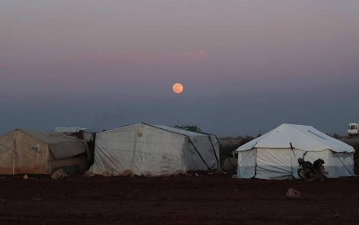 The moon is seen over tents in Azaz