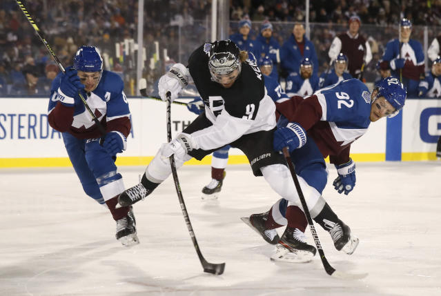Los Angeles Kings center Adrian Kempe, center, shoots the puck as Colorado Avalanche defenseman Erik Johnson, left, and left wing Gabriel Landeskog defend during the first period of an NHL hockey game Saturday, Feb. 15, 2020, at Air Force Academy, Colo. (AP Photo/David Zalubowski)