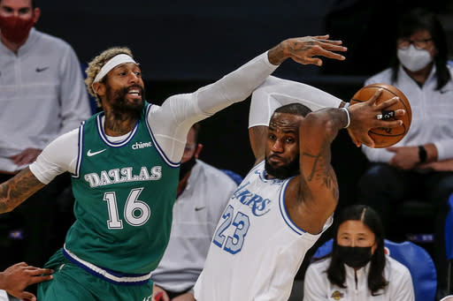 Los Angeles Lakers' LeBron James (23) looks to pass while under pressure from Dallas Mavericks' James Johnson (16) during the first half of an NBA basketball game Friday, Dec. 25, 2020, in Los Angeles. (AP Photo/Ringo H.W. Chiu)