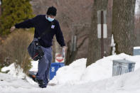 Postal carrier Josiah Morse steps carefully on a snowy sidewalk, Wednesday, Feb. 3, 2021, in Portland, Maine. The U.S. Postal Service's stretch of challenges didn't end with the November general election and tens of millions of mail-in votes. The pandemic-depleted workforce fell further into a hole during the holiday rush, leading to long hours and a mountain of delayed mail. (AP Photo/Robert F. Bukaty)