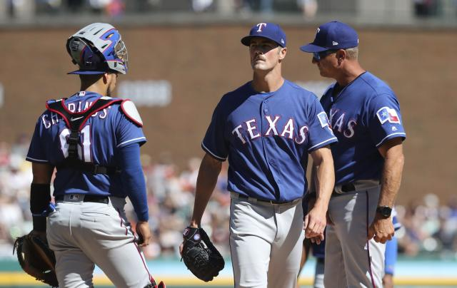 Texas Rangers starting pitcher Cole Hamels, center, walks to the dugout after being relieved during the first inning of a baseball game against the Detroit Tigers, Saturday, July 7, 2018, in Detroit. (AP Photo/Carlos Osorio)