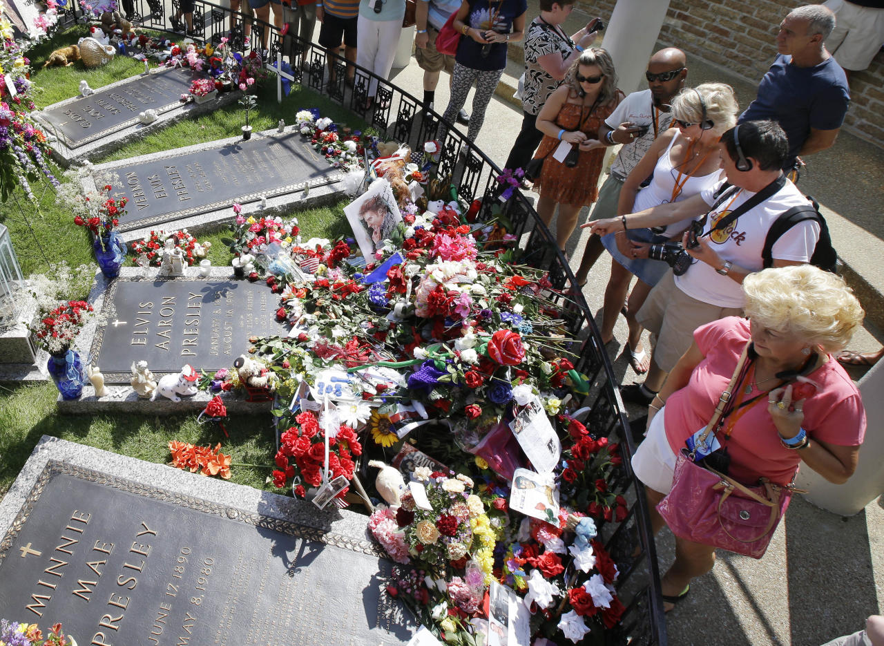 FILE - In this Aug. 16, 2012, file photo, Elvis Presley fans visit his grave at Graceland, Presley's Memphis, Tenn., home. The operators of Graceland said the tourist attraction centered on the life and music of Elvis Presley has received its 20 millionth paid visitor Monday, May 2, 2016. (AP Photo/Mark Humphrey, File)
