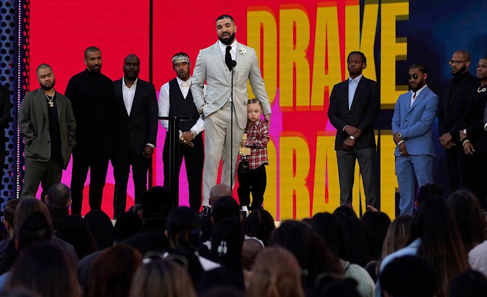 Friends and family look on as Drake accepts the artist of the decade award while he holds his son Adonis Graham.