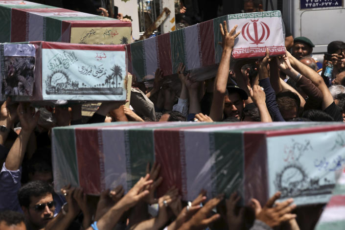 Mourners carry flag-draped caskets in a mass funeral procession for 150 soldiers killed during the war with Iraq in the 1980s, as well as two others killed in Syria in 2016, whose remains were recently recovered in the battlefields, in Tehran, Iran, Thursday, June 27, 2019. (AP Photo/Vahid Salemi)