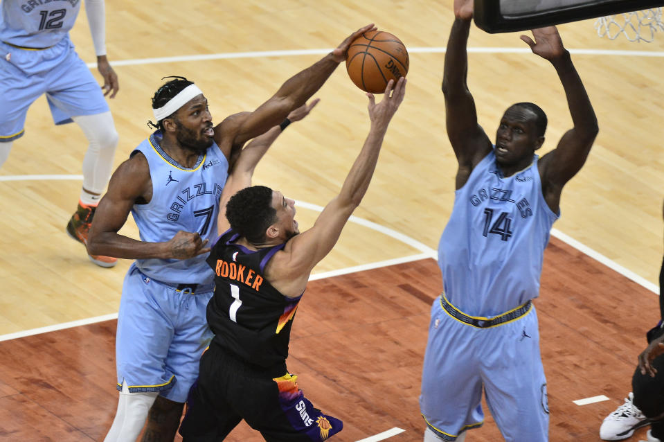 Phoenix Suns guard Devin Booker (1) shoots against Memphis Grizzlies forward Justise Winslow (7) as center Gorgui Dieng (14) defends in the first half of an NBA basketball game Saturday, Feb. 20, 2021, in Memphis, Tenn. (AP Photo/Brandon Dill)