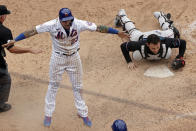 New York Mets' Javier Baez reacts after scoring the game winning run past Miami Marlins catcher Alex Jackson during the ninth inning of the first game of a baseball doubleheader that started April 11 and was suspended because of rain, Tuesday, Aug. 31, 2021, in New York. The Mets won 6-5. (AP Photo/Adam Hunger)
