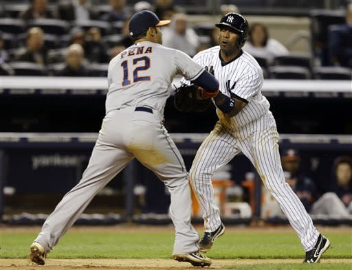 Houston Astros' Carlos Pena (12) tags out New York Yankees' Eduardo Nunez, who was trying to score on Brett Gardner's sixth-inning fielder's choice, in a baseball game at Yankee Stadium in New York, Tuesday, April 30, 2013. (AP Photo/Kathy Willens)