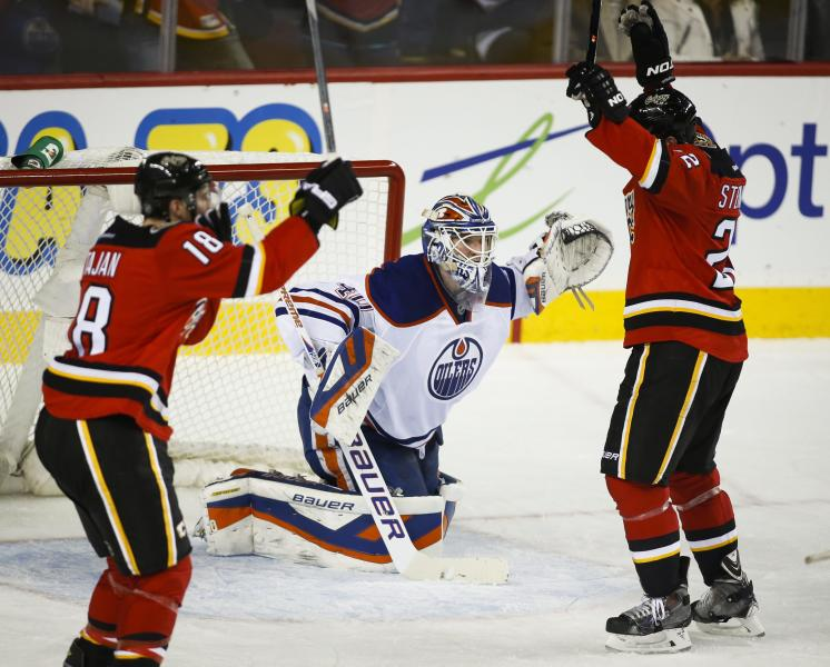 Edmonton Oilers goalie Devan Dubnyk, centre, reacts as Calgary Flames' Matt Stajan, left, and Lee Stempniak celebrate a Flames' goal during second period NHL hockey action in Calgary, Alberta. (AP Photo/The Canadian Press, Jeff McIntosh)