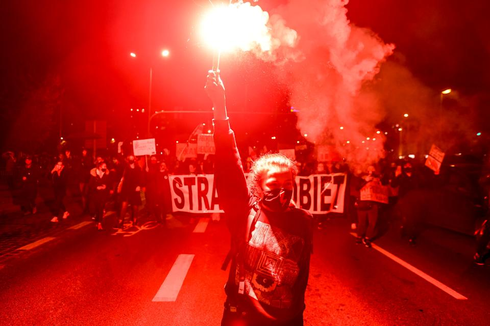A demonstrator holds a flare during a protest against the ruling by Poland's Constitutional Tribunal that imposes a near-total ban on abortion, in Wroclaw, Poland October 26, 2020. Picture taken October 26, 2020. Tomasz Pietrzyk/Agencja Gazeta via REUTERS ATTENTION EDITORS - THIS IMAGE WAS PROVIDED BY A THIRD PARTY. POLAND OUT. NO COMMERCIAL OR EDITORIAL SALES IN POLAND.