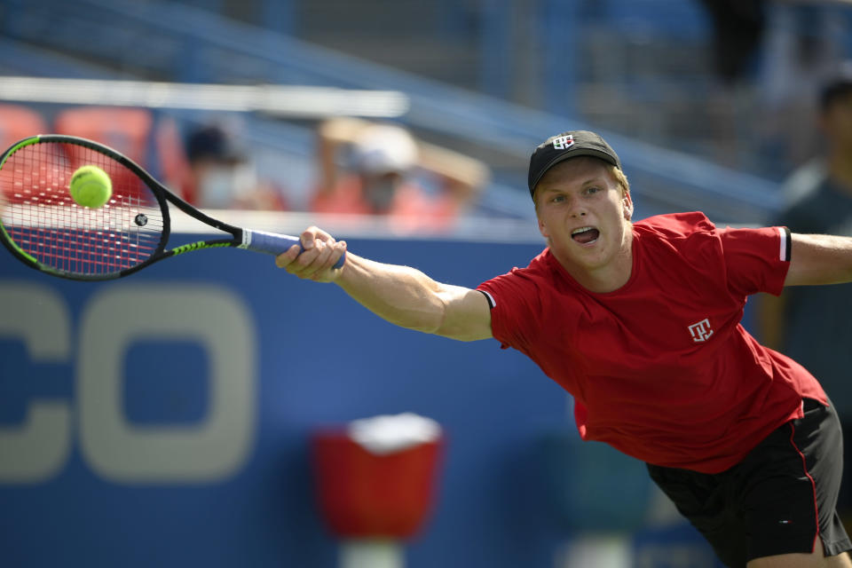 Jenson Brooksby reaches for the ball against against Kevin Anderson, of South Africa, during a match in the Citi Open tennis tournament, Monday, Aug. 2, 2021, in Washington. (AP Photo/Nick Wass)