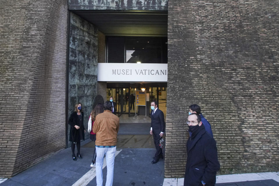 The first visitors of the day enter the Vatican Museums, at the Vatican, Monday, Feb. 1, 2021. The Vatican Museums reopened Monday to visitors after 88 days of shutdown following COVID-19 containment measures. (AP Photo/Andrew Medichini)