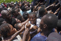 Residents crowd in front of a truck loaded with relief supplies in Vye Terre, Haiti, Friday, Aug. 20, 2021. Private aid and shipments from the U.S. government and others were arriving in the country's southwestern peninsula that was struck by a 7.2 magnitude quake on Aug. 14. (AP Photo/Fernando Llano)