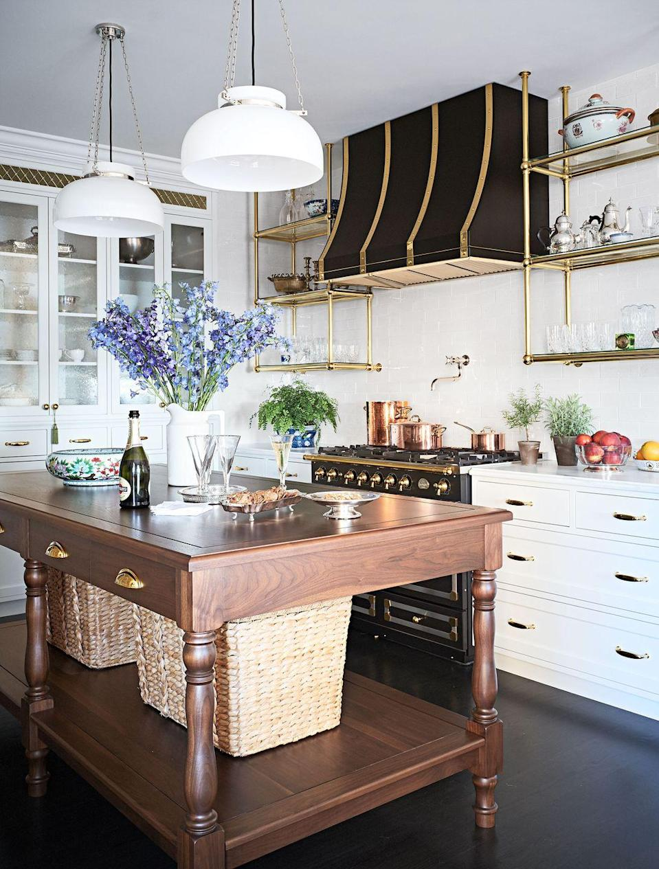 "<p>The decorative brass grilles and accents around the stovetop, plus the white pendant lights give this renovated kitchen by Summer Thornton a <a href=""https://www.housebeautiful.com/design-inspiration/house-tours/a25647684/summer-thornton-chicago-apartment-tour-transformation/"" rel=""nofollow noopener"" target=""_blank"" data-ylk=""slk:French brasserie"" class=""link rapid-noclick-resp"">French brasserie</a> feel. Storage baskets under the kitchen island table dress things down just a touch. </p>"