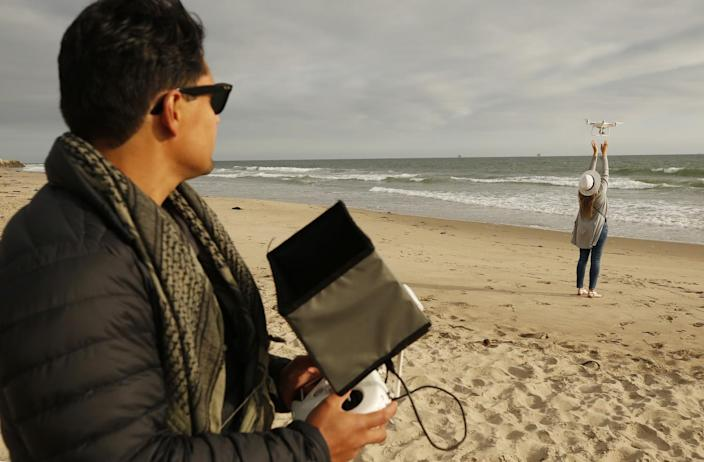Drone photographer Carlos Gauna, with the assistance from his wife, Andressa, launches a drone