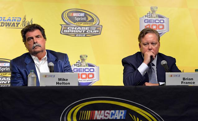 NASCAR Chairman and CEO Brian France, right, and NASCAR President Mike Helton, listen to questions during a press conference during practice for the NASCAR Sprint Cup Series auto race at Chicagoland Speedway in Joliet, Ill., Friday, Sept. 13, 2013. NASCAR added driver Jeff Gordon to the Chase championship field, and placed Penske Racing and Front Row on probation.(AP Photo/Nam Y. Huh)