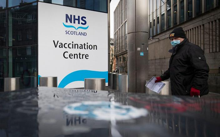 Members of the public pass an NHS Scotland vaccination centre set up at the Edinburgh International Conference Centre (EICC) in Edinburgh - JANE BARLOW/PA
