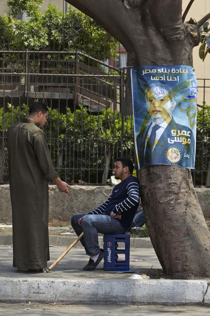 "Two followers of Egyptian Muslim cleric and former candidate for the Egyptian presidency Hazem Salah Abu Ismail rest in shade next to an election poster of presidential candidate Amr Moussa with Arabic that reads, ""rebuilding Egypt, we can do it, Amr Moussa,"" in Cairo, Egypt, Tuesday, May 1, 2012. (AP Photo/Fredrik Persson)"