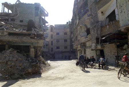 Civilians sit near damaged buildings at the Palestinian refugee camp of Yarmouk, south of Damascus, February 12, 2014. Picture taken February 12, 2014. REUTERS/Mohamad Mohamad