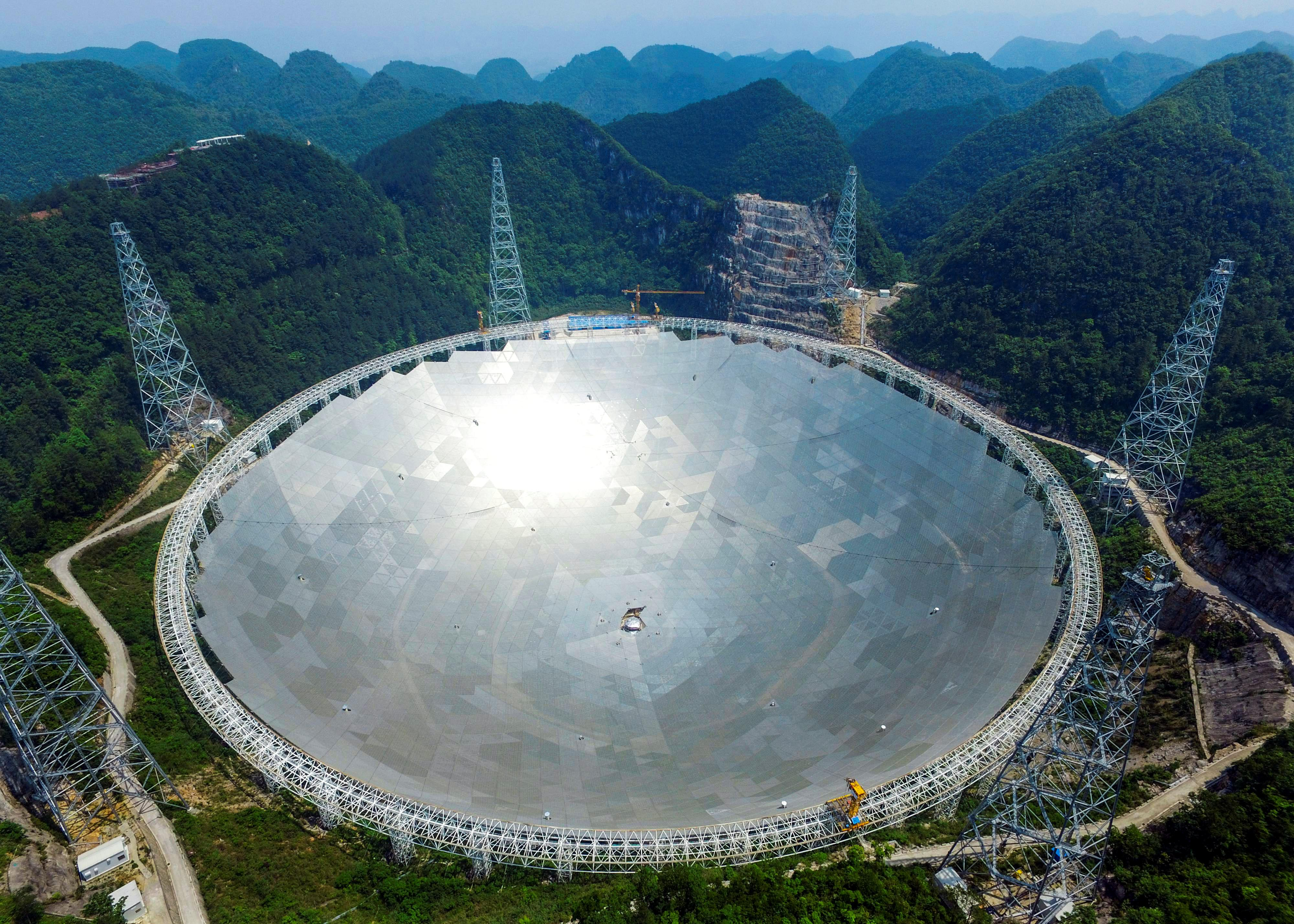 A 500-metre (1,640-ft.) aperture spherical telescope (FAST) is seen at the final stage of construction, among the mountains in Pingtang county, Guizhou province, China, May 7, 2016. REUTERS/Stringer ATTENTION EDITORS - THIS IMAGE WAS PROVIDED BY A THIRD PARTY. EDITORIAL USE ONLY. CHINA OUT. NO COMMERCIAL OR EDITORIAL SALES IN CHINA. TPX IMAGES OF THE DAY