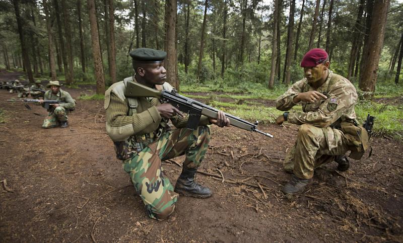 FILE - In this Thursday, Dec. 5, 2013 file photo, corporal Andrew Smith of Britain's 3rd Battalion, The Parachute Regiment, right, instructs rangers of the Kenya Wildlife Service and Kenya Forest Service about the use of hand signals while patrolling, as they stage a demonstration of the skills they have learned over the last few days of joint anti-poaching training, in the forest near Nanyuki, Kenya Thursday, Dec. 5, 2013. Africa is getting tougher in its fight against poaching with new laws with stiff penalties, more military training for rangers, and new technology like drones with thermal cameras are all helping to protect rhinos and elephants. (AP Photo/Ben Curtis, File)