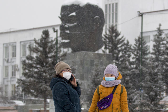 Two women wearing face masks to protect against coronavirus stand in front of a monument of Vladimir Lenin in Ulan-Ude, the regional capital of Buryatia, a region near the Russia-Mongolia border, Russia, Friday, Nov. 20, 2020. Russia's health care system has been under severe strain in recent weeks, as a resurgence of the coronavirus pandemic has swept the country. (AP Photo/Anna Ogorodnik)