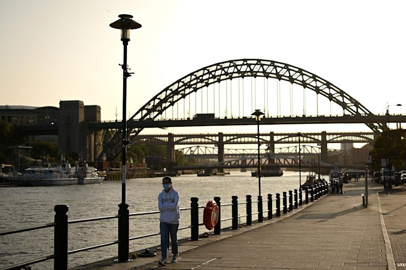 A woman wearing a protective face mask walks along the quayside, on the banks of the River Tyne, backdropped by the Tyne Bridge in Newcastle. (Photo: OLI SCARFF via Getty Images)
