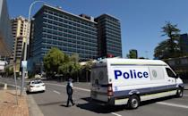 Police block off the scene near New South Wales Police Headquarters where a 15-year-old gunman shot dead a civilian police employee the previous day, before being gunned down by police in Sydney on October 3, 2015