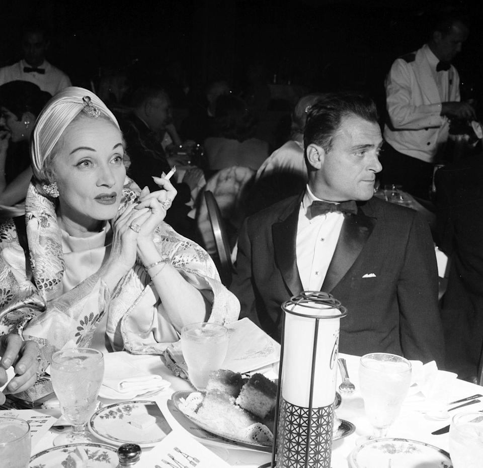 <p>Ever the style maven, Dietrich and Mike Todd enjoy a dinner in Los Angeles, with her making a statement with a satin, jewel-encrusted turban and floral dinner jacket. <br></p>