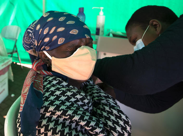 A retiree receives the first dose of the Pfizer coronavirus vaccine from a health worker inside a tent, during a mass vaccination program for the elderly at the clinic outside Johannesburg, South Africa, Monday, May 24, 2021. South Africa aims to vaccinate 5 million of its older citizens by the end of June. (AP Photo/Themba Hadebe)