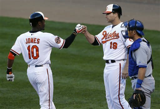 Baltimore Orioles' Adam Jones, left, fist bumps teammate Chris Davis in front of Toronto Blue Jays catcher Jeff Mathis after Jones batted Davis in on a home run in the fourth inning of the first baseball game of a doubleheader in Baltimore, Monday, Sept. 24, 2012. (AP Photo/Patrick Semansky)