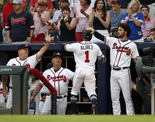 Atlanta Braves' Ozzie Albies (1) is greeted at the dugout entrance by hitting coach Kevin Seitzer, left, manager Brian Snitker and Dansby Season after scoring on a Nick Markakis double in the first inning of a baseball game against the Milwaukee Brewers, Friday, Aug. 10, 2018, in Atlanta. (AP Photo/John Bazemore)