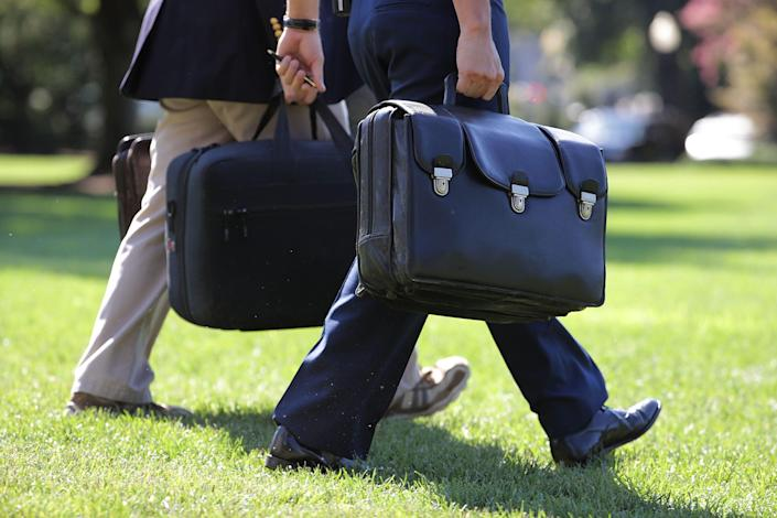 "A military aide carries the ""football,"" a case with he launch codes for nuclear weapons, as he follows President Obama across the South Lawn of the White House before boarding Marine One Aug.  23, 2016"