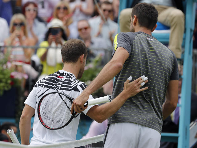 Marin Cilic of Croatia, right, and Diego Schwartzman of Argentina leave the court after their singles match at the Queens Club tennis tournament in London, Thursday, June 20, 2019. (AP Photo/Frank Augstein)