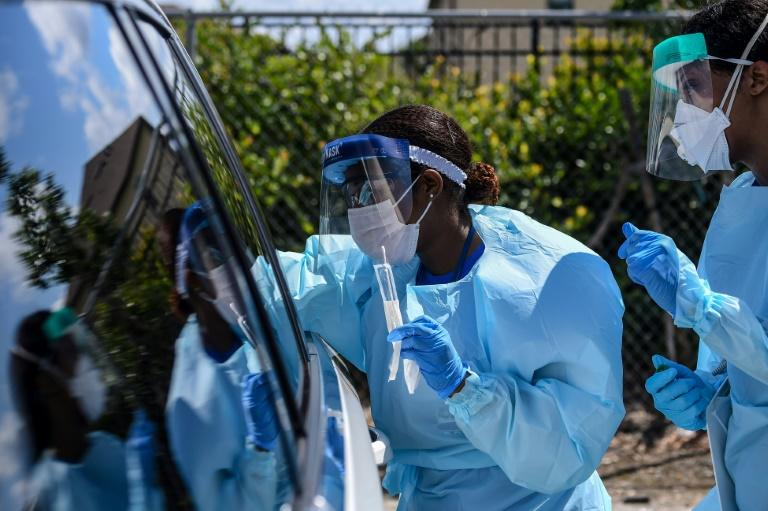 """Medical personnel take samples at a """"drive-thru"""" coronavirus testing lab set up by local community centre in West Palm Beach, north of Miami (AFP Photo/CHANDAN KHANNA)"""