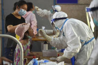A nurse takes swab samples in the new rounds of Covid-19 testing in Nanjing in eastern China's Jiangsu province Monday, Aug. 2, 2021. China's worst coronavirus outbreak since the start of the pandemic a year and a half ago escalated Wednesday, Aug. 4, 2021 with dozens more cases around the country, the sealing-off of one city and the punishment of its local leaders. (Chinatopix Via AP)
