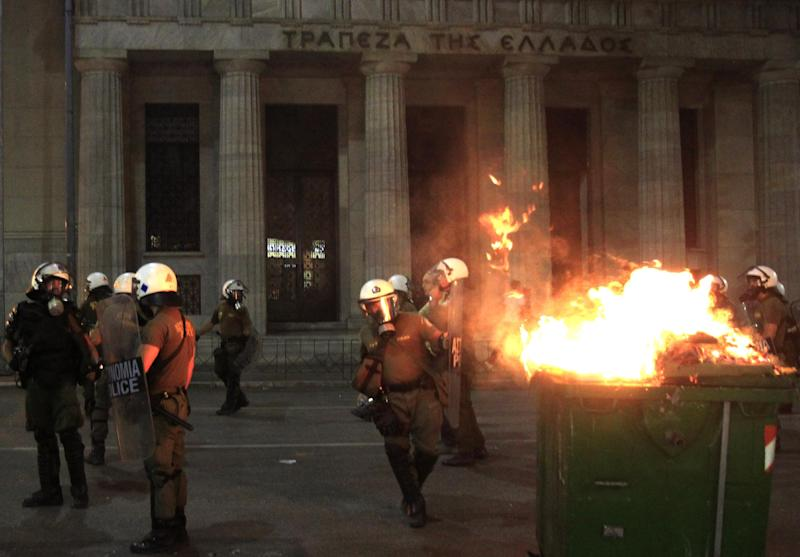 Riot police walk past a burning garbage bin in front of the Bank of Greece during a protest in Thessaloniki, Wednesday, Sept. 18, 2013. Violent clashes broke out Wednesday in several Greek cities after a member of the country's far-right Golden Dawn party was arrested in the fatal stabbing of a 34-year-old musician described as an anti-fascist activist. The stabbing drew condemnation from across Greece's political spectrum and from abroad. While the extremist Golden Dawn has been blamed for numerous violent attacks in the past, the overnight stabbing is the most serious violence directly attributed to a member so far. (AP Photo/Nikolas Giakoumidis)