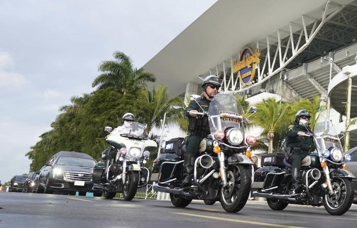 The hearse carrying the casket of FBI Special Agent Laura Schwartzenberger leaves with a police escort after a memorial service at Hard Rock Stadium on Saturday, Feb. 6, 2021, in Miami Gardens, Fla. Schwartzenberger and Special Agent Daniel Alfin were killed while serving a warrant this week in Sunrise, Fla. (AP Photo/Hans Deryk)
