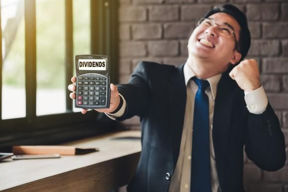 Smiling and fist-pumping businessman holds up a calculator, its display showing the word DIVIDENDS.
