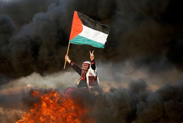 A woman waves a Palestinian flag during a protest calling for lifting the Israeli blockade on Gaza and demanding the right to return to their homeland, at the Israel-Gaza border fence east of Gaza City September 28, 2018. (Photo: Mohammed Salem/Reuters)