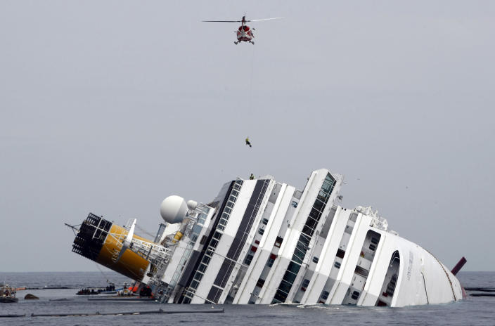 FILE - In this Tuesday, Jan. 31, 2012 file photo, an Italian firefighter is lowered from a helicopter onto the grounded Costa Concordia cruise ship off the Tuscan island of Giglio, Italy. An Italian court on Saturday, July 20, 2013 accepted plea bargains for five Costa Crociere employees in the Costa Concorda shipwreck that killed 32 crew and passengers, convicting all of multiple manslaughter and negligence. (AP Photo/Pier Paolo Cito, File)