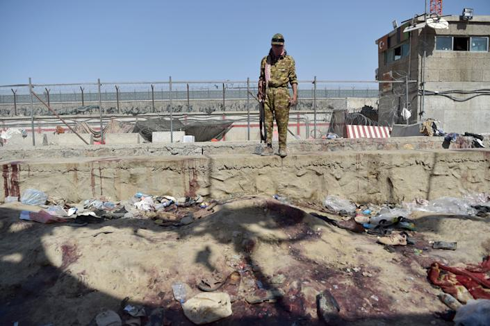 A Taliban fighter stands guard at the site of the August 26 twin suicide bombs, which killed scores of people including 13 US troops, at Kabul airport on August 27, 2021. (Wakil Kohsar/AFP via Getty Images)