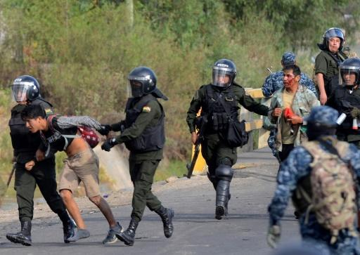 Bolivian riot police arrest Morales supporters during a protest against the interim government in Sacaba, Chapare province