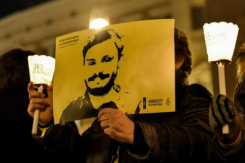 Activists of human rights organization Amnesty International hold a picture of Giulio Regeni and candles as they take part in a demonstration in front of Montecitorio, the Italian Parliament, in Rome on January 25, 2017