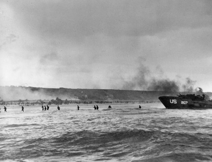 Under the cover of naval shell fire, American infantrymen wade ashore from their landing craft during the initial Normandy landing operations in France on June 6, 1944. (Photo: AP)