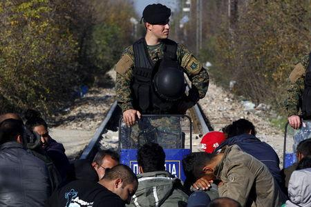 Migrants wait on the Greek side of the border with Macedonia as a Macedonian policeman stands guard on the Macedonian side, near the Greek village of Idomeni, November 19, 2015. REUTERS/Alexandros Avramidis