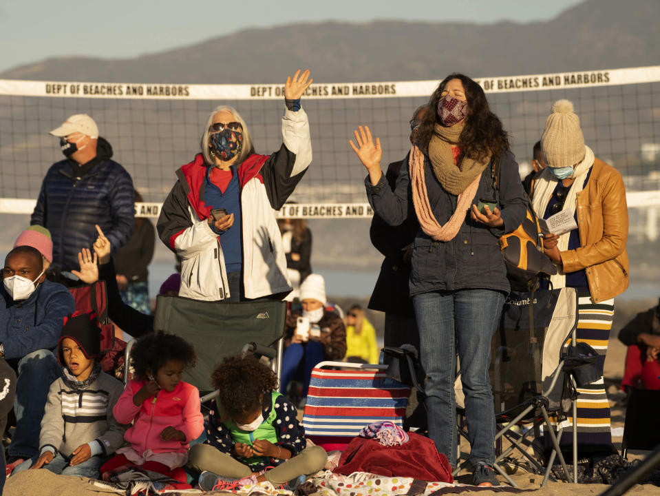 Members of the Veal family and friends join in praying during the Westside Easter Sunrise Service at Will Rogers State Beach park on the Santa Monica Bay on the Pacific Coast in the Pacific Palisades neighborhood of Los Angeles, Sunday, April 4, 2021. (AP Photo/Damian Dovarganes)