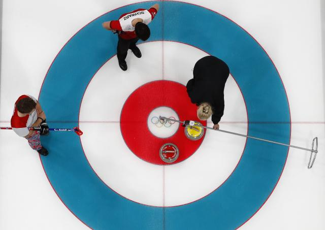 Curling - Pyeongchang 2018 Winter Olympics - Men's Round Robin - Switzerland v Norway - Gangneung Curling Center - Gangneung, South Korea - February 17, 2018 - Torger Nergaard of Norway and Benoit Schwarz of Switzerland watch as a games official uses a measuring device. REUTERS/Cathal McNaughton