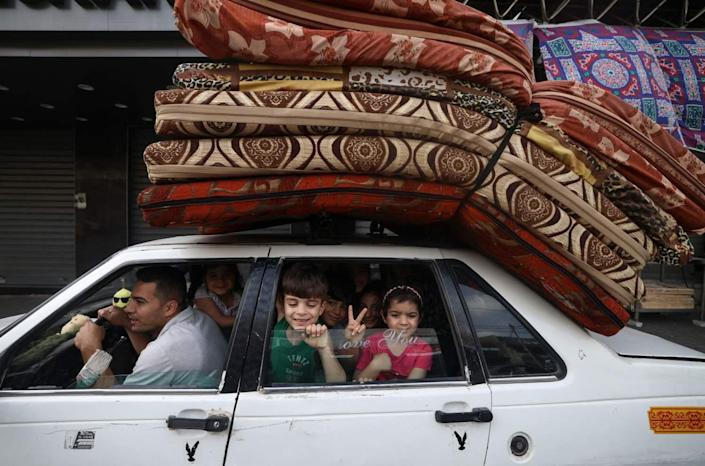A child flashes the V for victory sign from the back of a family's packed car