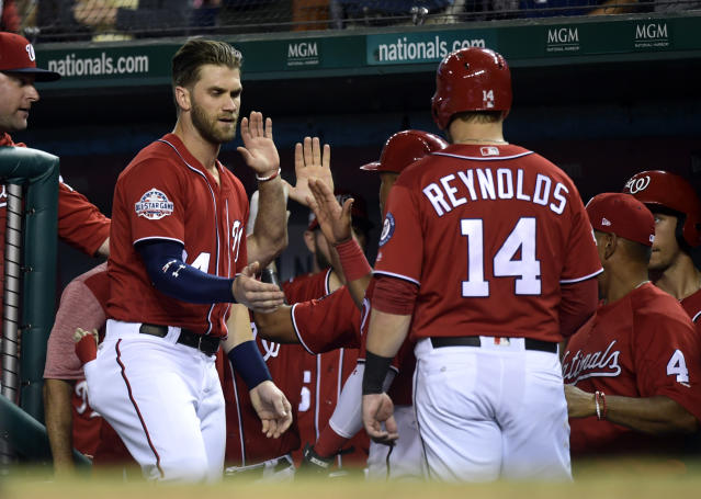 Washington Nationals Bryce Harper, second from left, reaches out to congratulate teammate Mark Reynolds, (14) after Reynolds hit a two-run home run against the Miami Marlins in the second inning of a baseball game at Nationals Park in Washington, Saturday, July 7, 2018. (AP Photo/Susan Walsh)